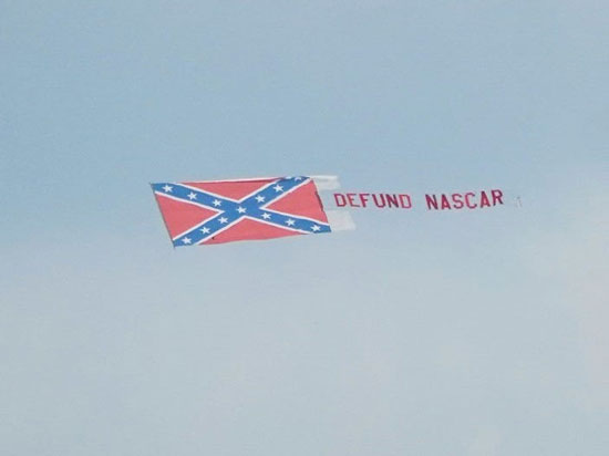 Defund NASCAR banner behind a plane at a NASCAR event.
